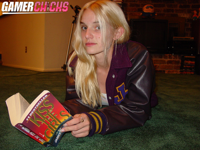 Blonde glamour teen model Liz Ashley poses in her purple senior jacket from Jersey Village High School for a bit while reading some hardcore science novel.